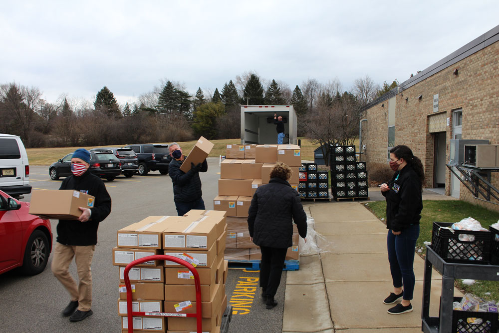 Volunteers loading vehicles with food